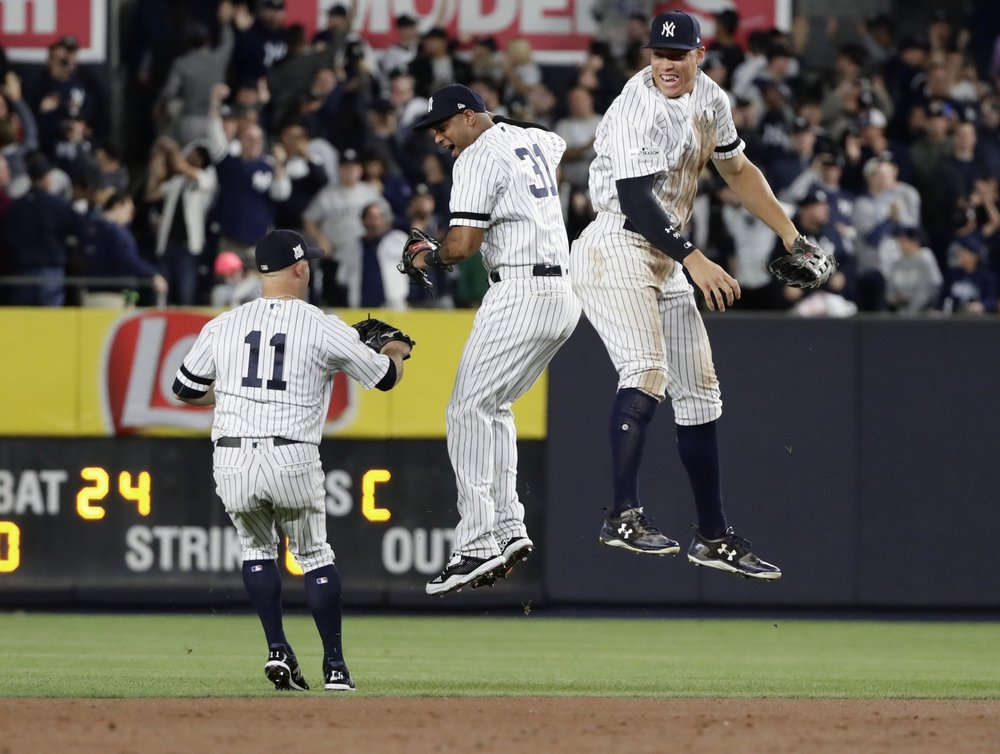 New York Yankees' Aaron Judge, right, celebrates with Aaron Hicks, center, as Brett Gardner, left, watches after the Yankees defeated the Minnesota Twins 8-4 in the American League wild-card baseball playoff game, early Wednesday, Oct. 4, 2017, in New York. (AP Photo/Frank Franklin II)