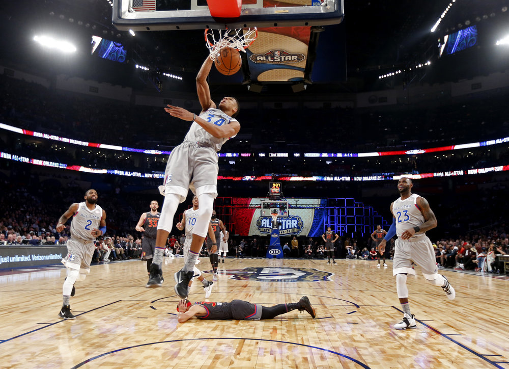Eastern Conference small forward Giannis Antetokounmpo, of the Milwaukee Bucks, dunks as Western Conference guard Stephen Curry, bottom, of the Golden State Warriors, lies on the court during the first half of the NBA All-Star basketball game in New Orleans (AP Photo/Max Becherer, Pool, File)