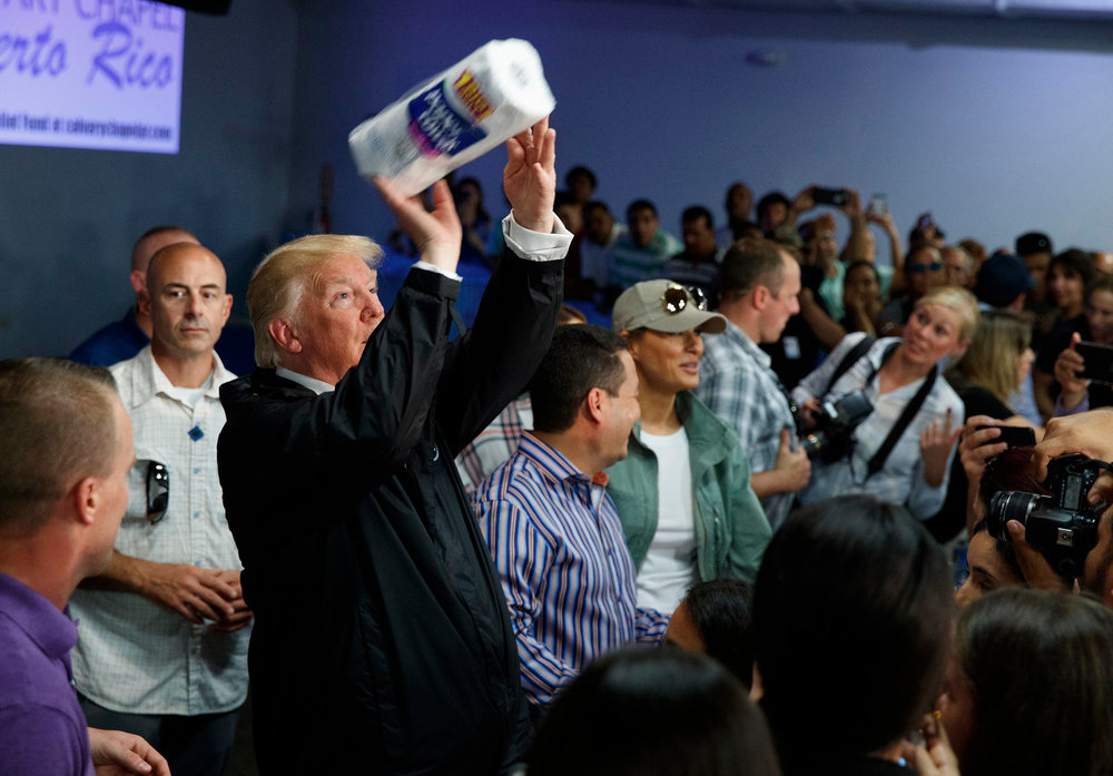 In this Tuesday, Oct. 3, 2017 photo, President Donald Trump tosses paper towels into a crowd at Calvary Chapel in Guaynabo, Puerto Rico. Trump helped sink Puerto Ricans bond prices with talk of wiping out the U.S. territory's debt but his budget director dismissed the idea of a bailout as the bankrupt island fights to recover from Hurricane Maria. (AP Photo/Evan Vucci)