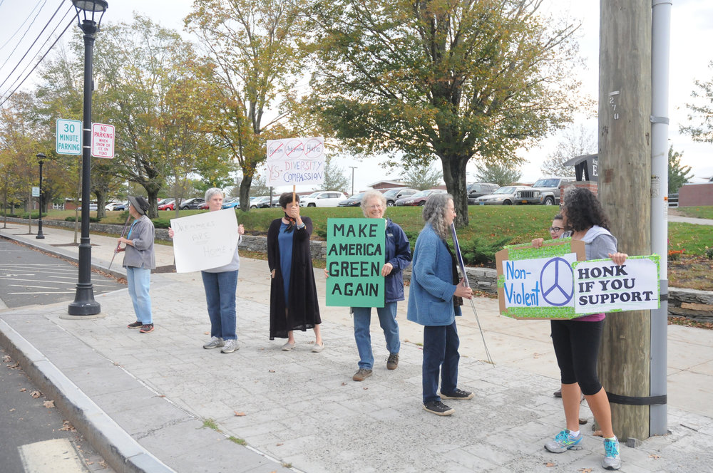 Members of the Mansfield community, some of them former E.O. Smith teachers, gather on the sidewalk in Storrs Center for a peaceful demonstration in support of social justice, refugees, immigrants, and health care for all. The vigils take place weekly on Wednesdays from 4:30-5:30. (Olivia Stenger/The Daily Campus)
