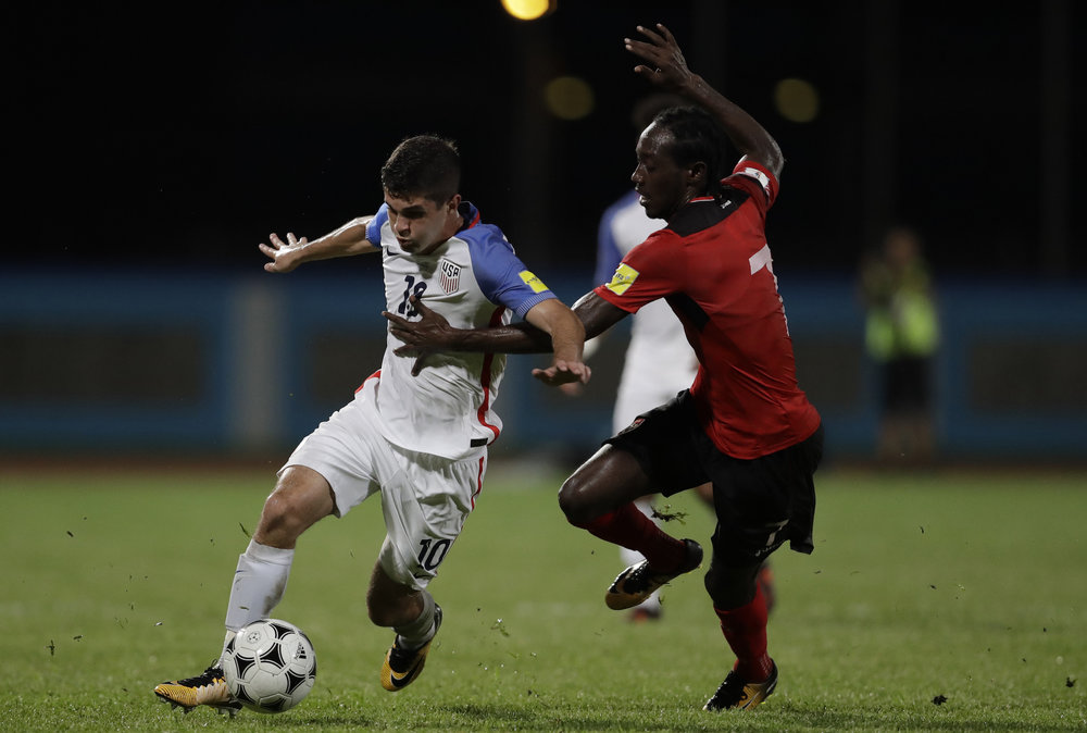 United States' Christian Pulisic, left, fight for the ball with Trinidad and Tobago's Nathan Lewis during a 2018 World Cup qualifying soccer match in Couva, Trinidad, Tuesday, Oct. 10, 2017. (AP Photo/Rebecca Blackwell)