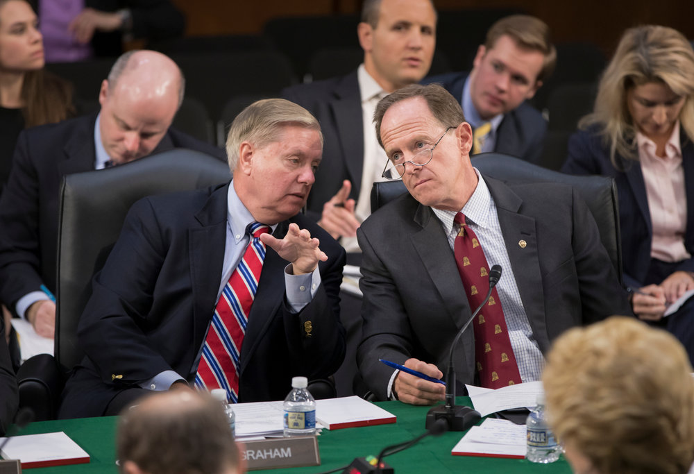 Sen. Lindsey Graham, R-S.C., left, confers with Sen. Pat Toomey, R-Pa., as the Senate Budget Committee votes on amendments during the markup of Senate's fiscal year 2018 budget resolution, on Capitol Hill in Washington, Thursday, Oct. 5, 2017. (AP Photo/J. Scott Applewhite