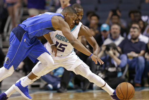 Charlotte Hornets' Kemba Walker (15) and Dallas Mavericks' Dennis Smith Jr. (1) chase a loose ball in the first half of a preseason NBA basketball game in Charlotte, N.C., Friday, Oct. 13, 2017. (AP Photo/Chuck Burton)