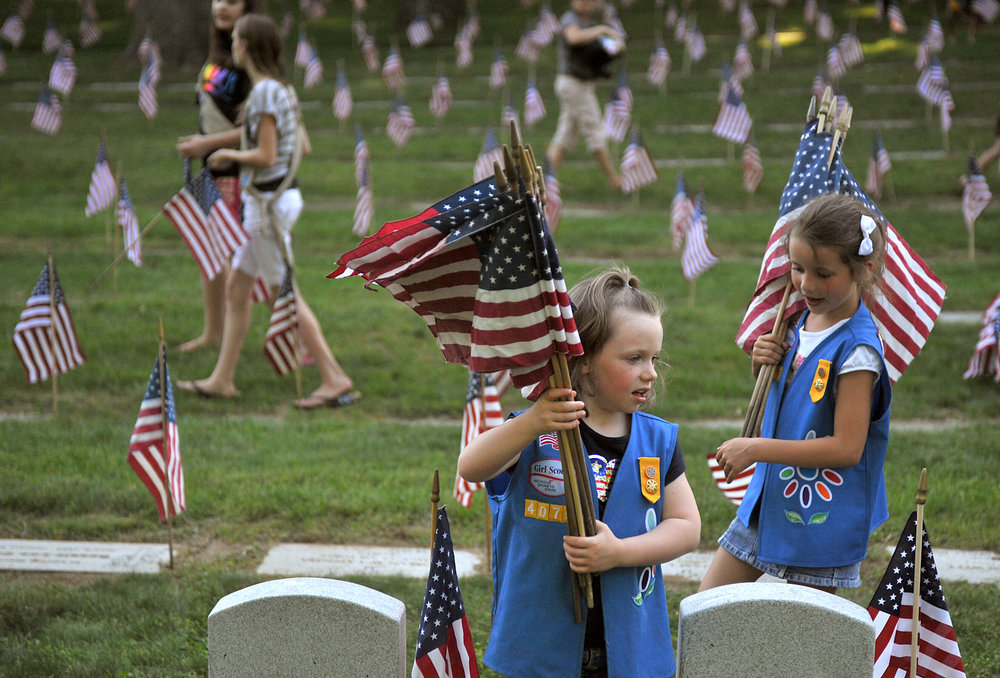 FILE - In this May 23, 2012 file photo, Natalie Benson, 5, and Holly Sweezer, 6, carry extra flags as Boy and Girl Scouts place flags on each of the 5,000 headstones at the Grand Rapids Veterans State Cemetery in Grand Rapids, Mich. (Katie Greene/The Grand Rapids Press via AP)