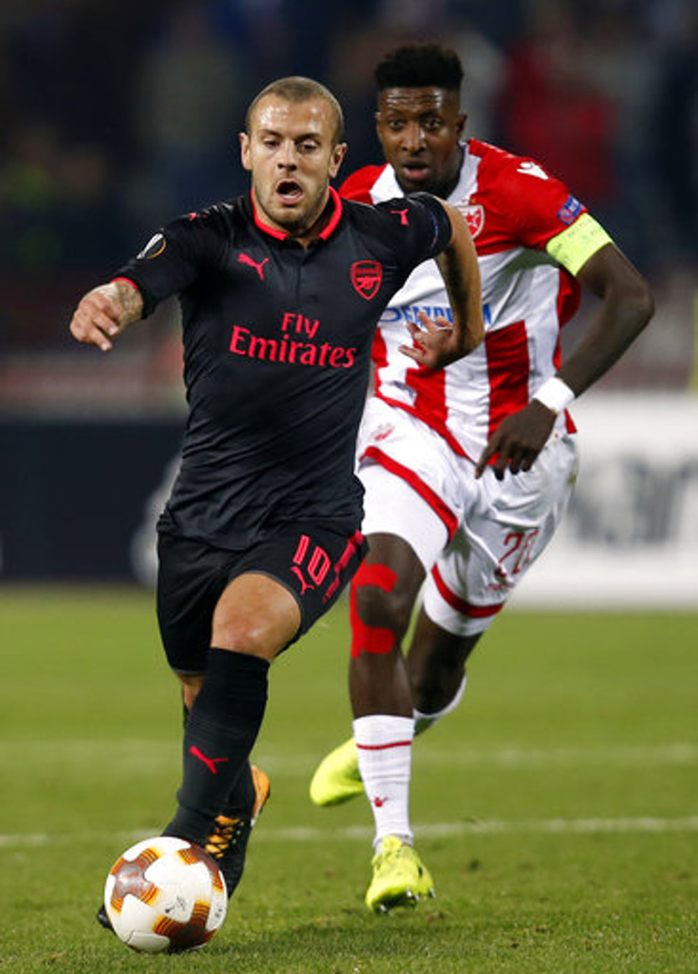 Arsenal's Jack Wilshere, front, challenges for the ball with Red Star's Mitchell Donald during the Europa League group H soccer match between Red Star and Arsenal on the stadium Rajko Mitic in Belgrade, Serbia, Thursday, Oct. 19, 2017. (Darko Vojinovic/AP)