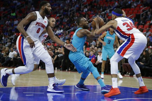 Charlotte Hornets guard Kemba Walker controls the ball between Detroit Pistons center Andre Drummond (0) and forward Tobias Harris (34) during the second half of an NBA basketball game, Wednesday, Oct. 18,2017, in Detroit. (AP Photo/Carlos Osorio)