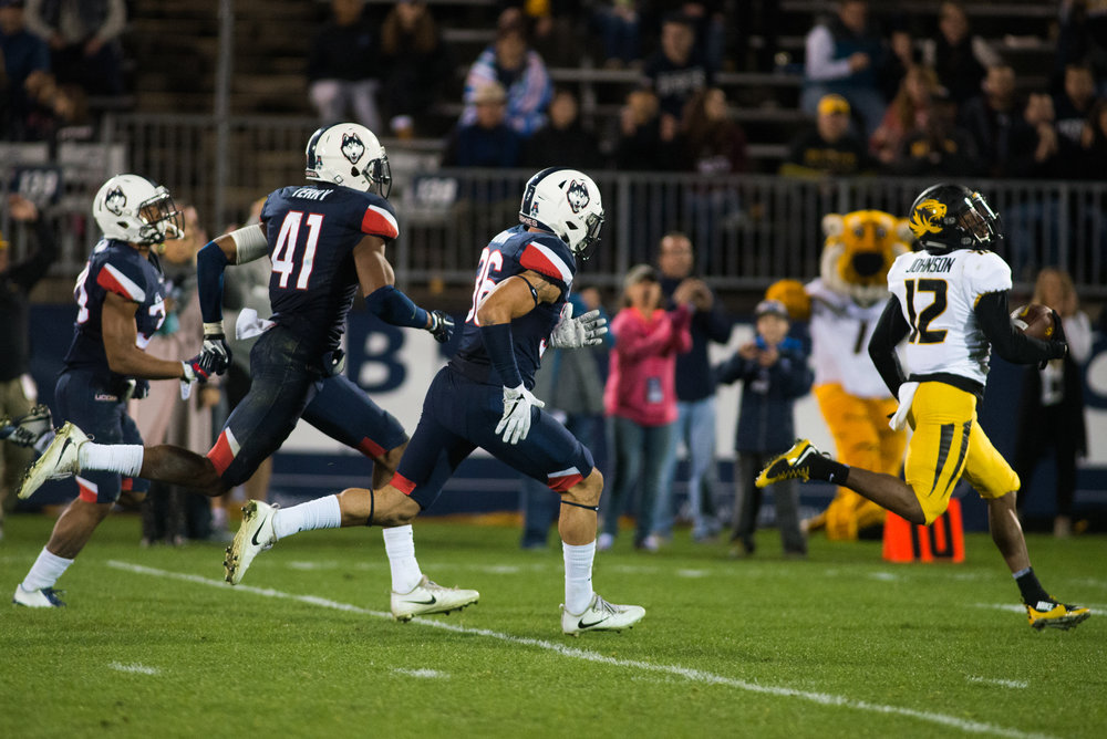 A trio of UConn defenders chase Missouri wide receiver Johnathon Johnson during the Huskies' 52-12 loss Saturday at Rentschler Field in East Hartford. (Amar Batra, Senior Staff Photographer/The Daily Campus)