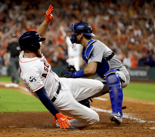 Houston Astros' Derek Fisher scores past Los Angeles Dodgers catcher Austin Barnes for the game-winning run during the 10th inning of Game 5 of baseball's World Series Monday, Oct. 30, 2017, in Houston. The Astros won 13-12 to take a 3-2 lead in the series.(AP Photo/Matt Slocum)