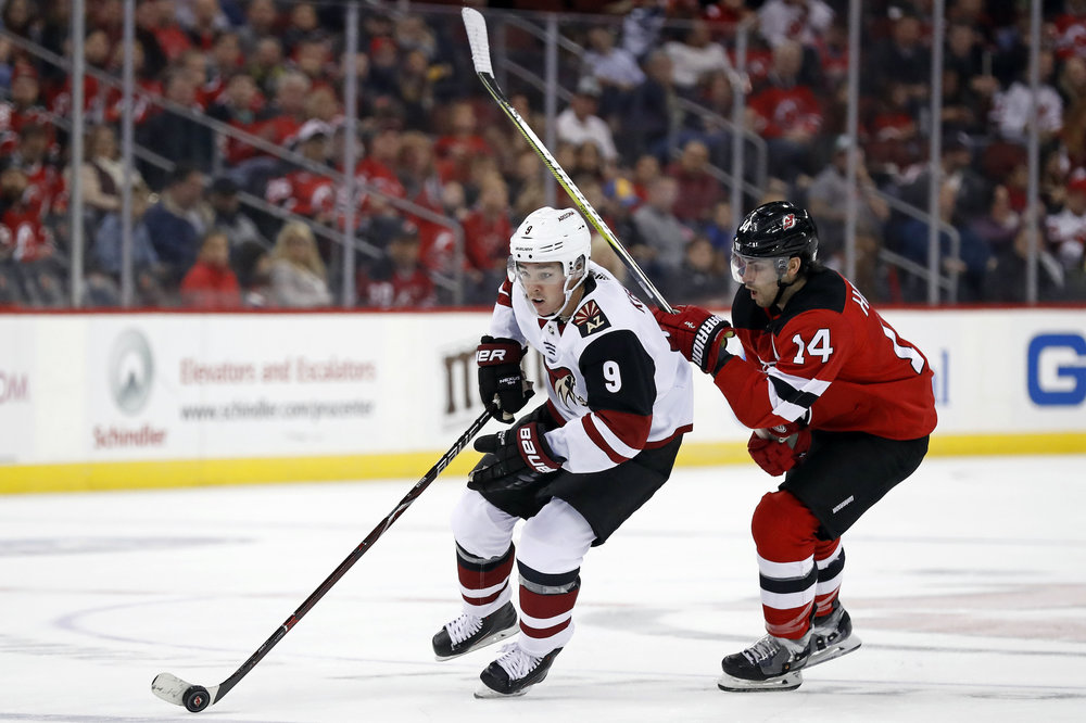 Arizona Coyotes' Clayton Keller (9) controls the puck past New Jersey Devils' Adam Henrique during the first period of an NHL hockey game, Saturday, Oct. 28, 2017, in Newark, N.J. (AP Photo/Adam Hunger)