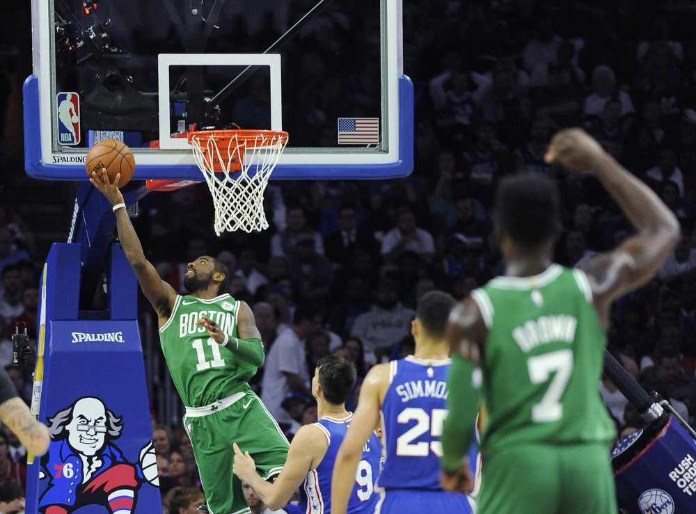 Boston Celtics' Kyrie Irving (11) drives to the basket past Philadelphia 76ers' Dario Saric (9) in the first half of an NBA basketball game, Friday, Oct. 20, 2017, in Philadelphia. (AP Photo/Michael Perez)