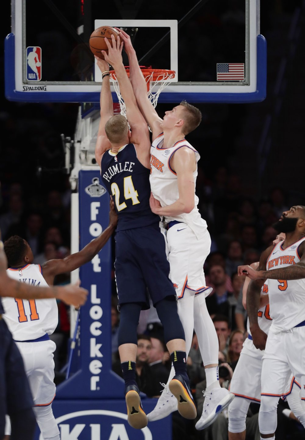 New York Knicks' Kristaps Porzingis, right, blocks a shot by Denver Nuggets' Mason Plumlee during the second half of an NBA basketball game Monday, Oct. 30, 2017, in New York. (AP Photo/Frank Franklin II)