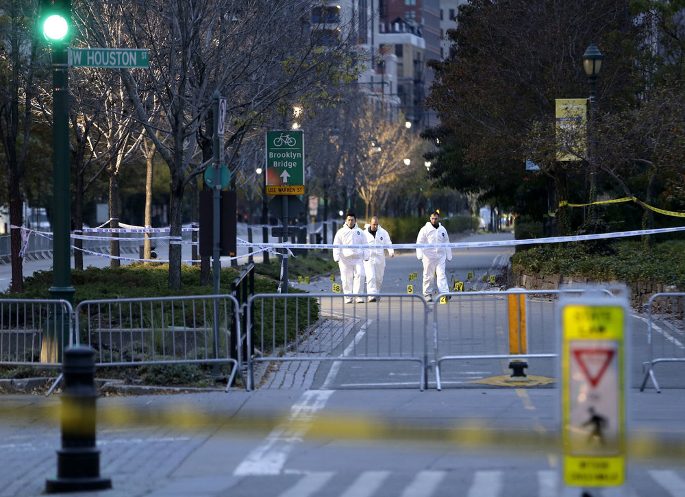Emergency officials walk near evidence markers on the west side bike path in lower Manhattan, New York, Wednesday, Nov. 1, 2017. Investigators worked through the night to determine what led a truck driver to plow down people Tuesday on the riverfront bike path near the World Trade Center, authorities said. (Seth Wenig/AP)