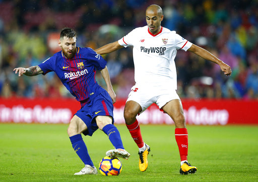 FC Barcelona's Lionel Messi, left, duels for the ball against Sevilla's Guido Pizarro during the Spanish La Liga soccer match between FC Barcelona and Sevilla at the Camp Nou stadium in Barcelona, Spain, Saturday, Nov. 4, 2017. (AP Photo/Manu Fernandez)