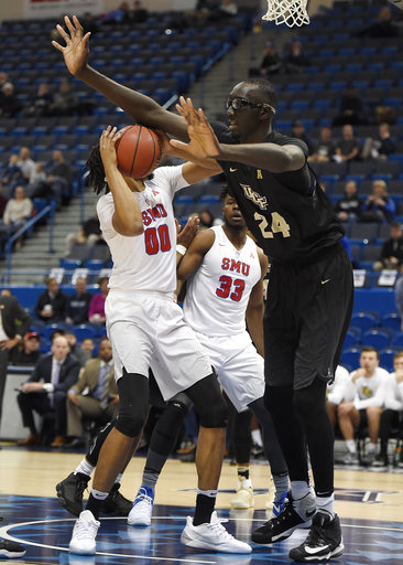 In this March 11, 2017, file photo, Central Florida's Tacko Fall, right, guards SMU's Ben Moore, left, during the first half of an NCAA college basketball game in the American Athletic Conference tournament semifinals, in Hartford, Conn. (AP Photo/Jessica Hill, File)