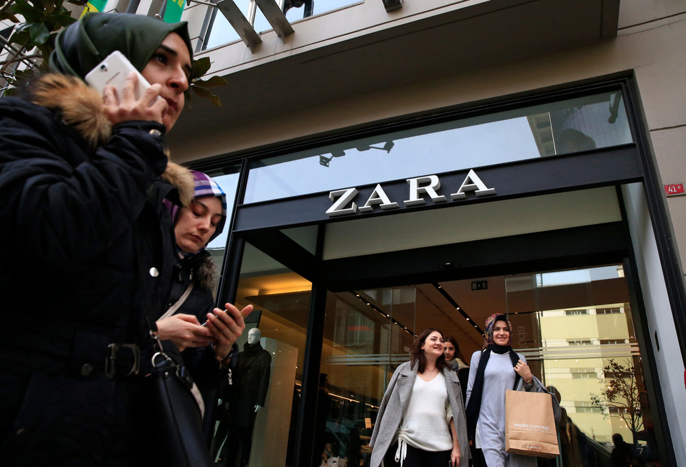 """People exit and walk past a fashion retailer Zara branch in an Istanbul upscale neighbourhood, Friday, Nov. 3, 2017. Shoppers at Zara in Istanbul have found unusual tags on their garments: put there by Turkish workers complaining they have not been paid for the manufacturing the merchandise in the store. Workers of an outsource manufacturer have been leaving tags inside clothes saying: """"I made this item you are going to buy, but I didn't get paid for it."""" (AP Photo/Lefteris Pitarakis)"""