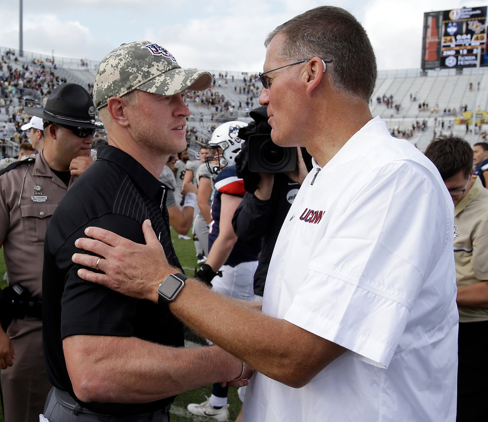 Central Florida head coach Scott Frost, left, and Connecticut head coach Randy Edsall shake hands at midfield after an NCAA college football game, Saturday, Nov. 11, 2017, in Orlando, Fla. Central Florida won 49-24. (AP Photo/John Raoux)