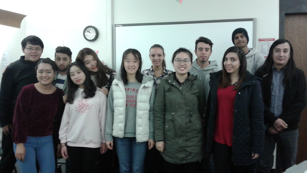 """These students are English language learners currently enrolled in the University of Connecticut American English Language Institute (UCAELI). They are working in a collaborative project with the Daily Campus in their Focus on Writing course where they were posed the following prompt: """"Share something that you'd like the UConn community to know about your country."""" (Photo courtsey of Krista Rogers)"""