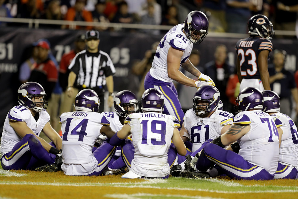 This Oct. 9, 2017 file photo shows Minnesota Vikings tight end Kyle Rudolph (82) celebrating a touchdown with his teammates during the second half of an NFL football game against the Chicago Bears in Chicago. Just as instructed in the huddle seconds earlier, his teammates sat down in a circle before he ran around and patted them on the helmet in a brief but humorous rendition of Duck, Duck, Goose. (Darron Cummings, file/AP)