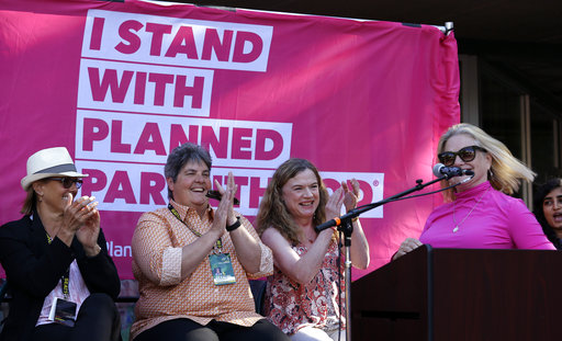 "FILE - In this July 18, 2017, file photo, Seattle Storm owners, from left, Ginny Gilder, Lisa Brummel and Dawn Trudeau, applaud speaker Christine Charbonneau, Planned Parenthood of the Great Northwest and the Hawaiian Islands CEO, as she speaks to a rally before the Storm's WNBA basketball game against the Chicago Sky, in Seattle. The WNBA once again leads all professional sports leagues in hiring women and minorities for coaching and front-office positions. The league earned a combined ""A"" grade for racial and gender diversity in its hiring practices, according to a report card issued Wednesday, Nov. 15, 2017, by The Institute for Diversity and Ethics in Sports (TIDES). (AP Photo/Elaine Thompson, File)"