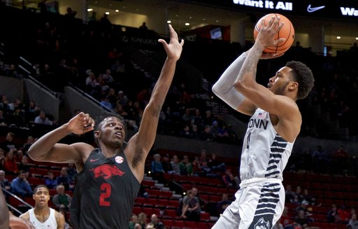 Connecticut guard Jalen Adams, right, shoots over Arkansas forward Adrio Bailey during the first half of an NCAA college basketball game in the Phil Knight Invitational tournament in Portland, Ore., Sunday, Nov. 26, 2017. (AP Photo/Craig Mitchelldyer)