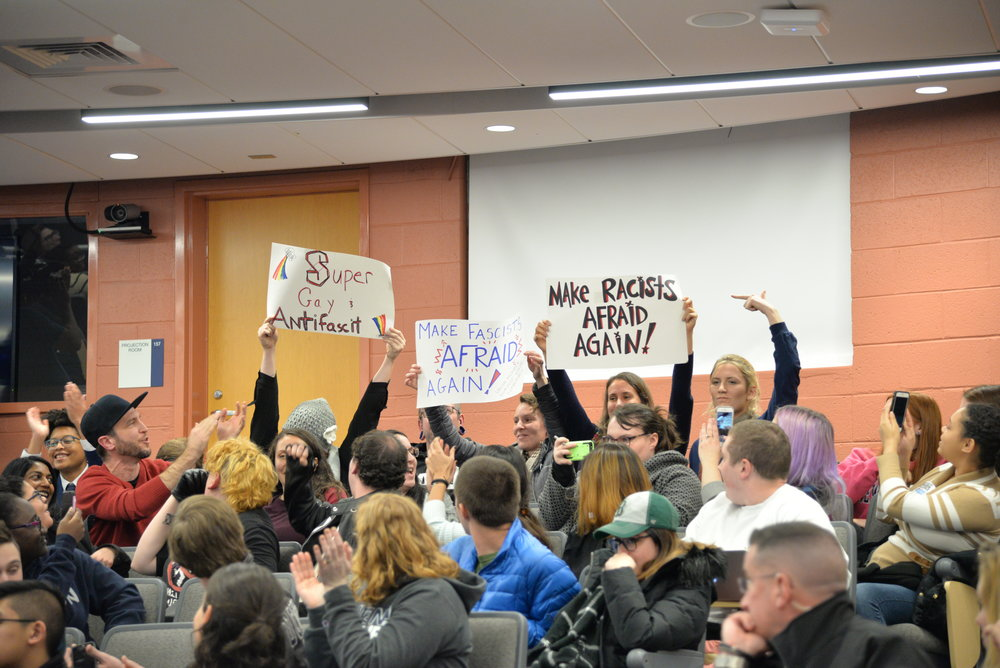 "Wintrich began firing back at the crowd, calling these signs in the audience, ""cute."" (Amar Batra/The Daily Campus)"