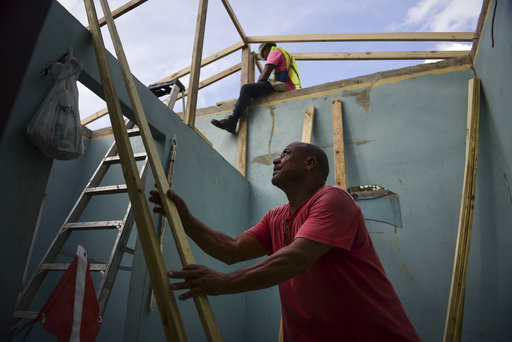 Pedro Deschamps helps workers hired by FEMA to carry out the installation of a temporary awning roof at his house, which suffered damage during Hurricane Maria, in San Juan, Puerto Rico, Wednesday, Nov. 15, 2017. (AP Photo/Carlos Giusti)