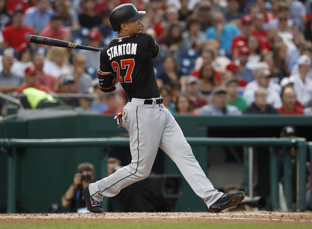 In this Aug. 10, 2017, file photo, Miami Marlins'Giancarlo Stanton (27) watches his two-run home run during the third inning of the team's baseball game against the Washington Nationals in Washington. (AP Photo/Carolyn Kaster, File)