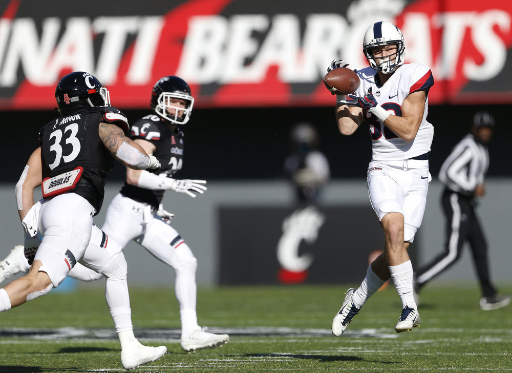 Connecticut wide receiver Mason Donaldson (82) catches a pass in front of Cincinnati linebacker Jaylyin Minor (33) during the first half of an NCAA college football game, Saturday, Nov. 25, 2017, in Cincinnati. (AP Photo/Gary Landers)