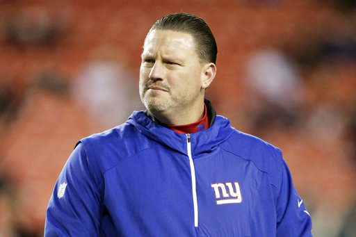 "FILE - In this Nov. 23, 2017, file photo, New York Giants coach Ben McAdoo stands on the field before the team's NFL football game against the Washington Redskins in Landover, Md. The Giants have little to play for and have already started planning for the future by benching two-time Super Bowl winning quarterback Eli Manning in order to get the opportunity to take a look at Geno Smith on Sunday against the Raiders and rookie Davis Webb down the road. It's a decision that was extremely unpopular in New York among fans who remember Manning's Super Bowl success and former players upset about the treatment of one of the franchise's most important players. ""The decision is bigger than me. It's for the organization and the future of the organization, making sure we have a clear evaluation of the other two quarterbacks on the roster,"" McAdoo said. (AP Photo/Mark Tenally, File)"