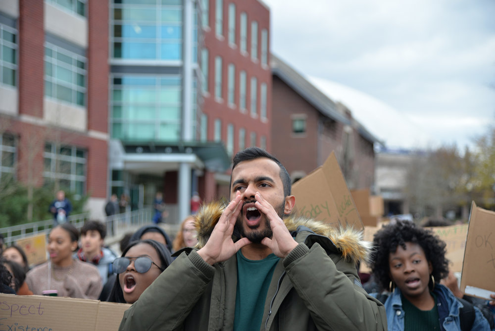Event organizer Ven Gopal leads a chant as students march through the center of campus towards Wilbur Cross in order to make their prescence known. (Amar Batra/The Daily Campus)