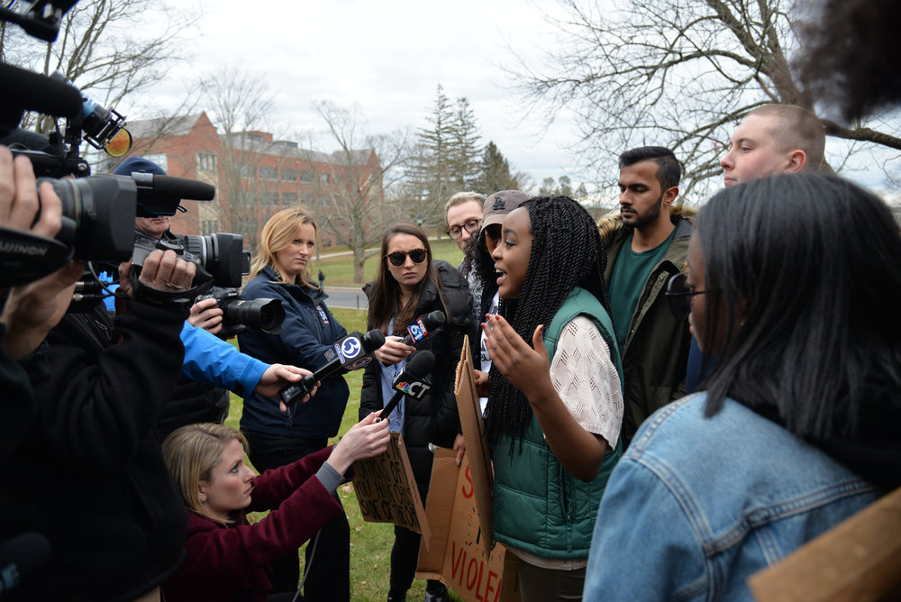 Event organizer Wawa Gatheru answers questions from the media and discusses the change that organizers want to see following the March for Action. Student activists and leaders stood in front of Wilbur Cross and demanded that university administration do something to make things safer on campus. (Amar Batra/The Daily Campus)