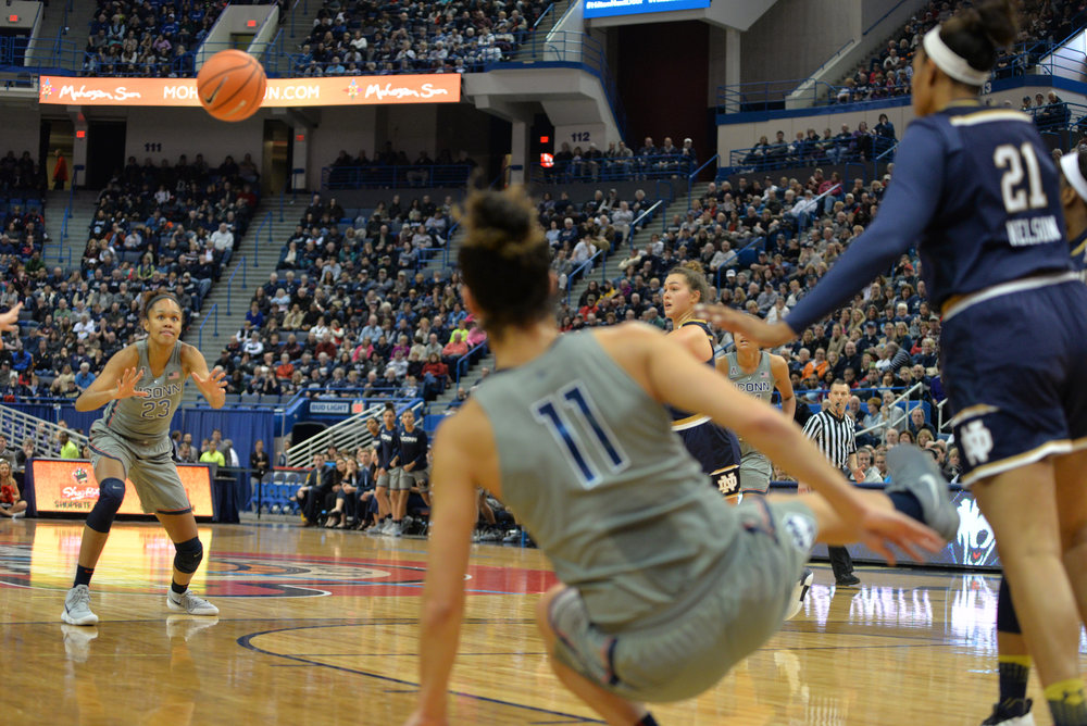 Kia Nurse passes the ball to Azura Stevens to prevent the ball from going out of bounds. (Amar Batra/The Daily Campus)