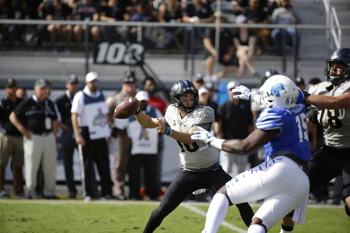 Central Florida quarterback McKenzie Milton looks for a receiver against Memphis during the first half of the American Athletic Conference championship NCAA college football game, Saturday, Dec. 2, 2017, in Orlando, Fla. (AP Photo/John Raoux)
