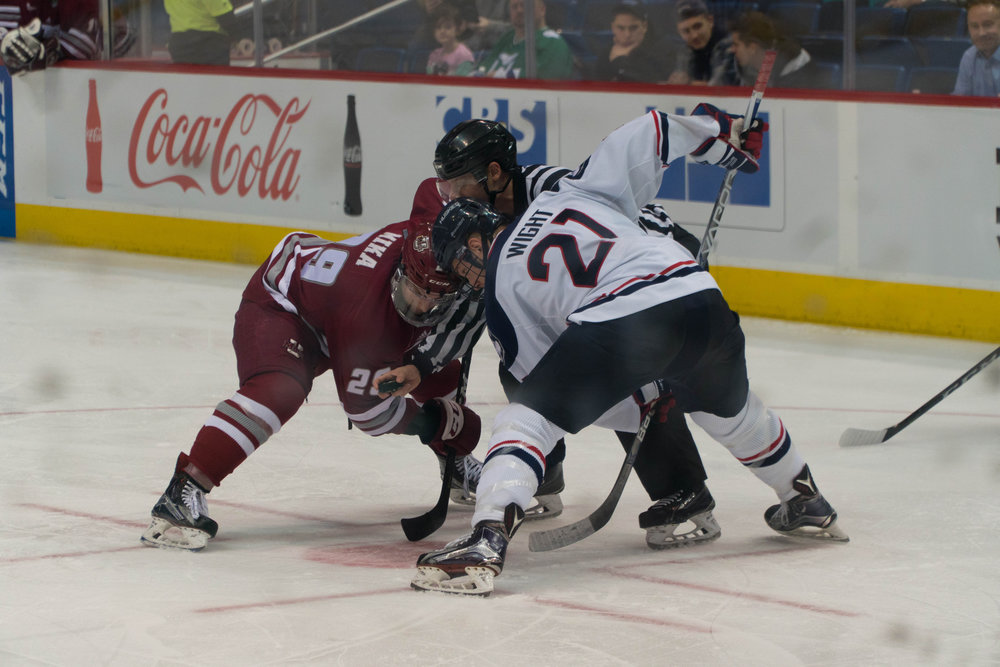 Forward Jeff Wight (21) squares off with a UMass hockey player on Tuesday night during the Huskies 8-2 victory over the UMass Minuteman at the XL Center. Wight scored the Huskies third goal of the evening.