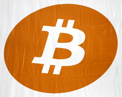 FILE - In this Monday, April 7, 2014, file photo, a bitcoin logo is displayed at the Inside Bitcoins conference and trade show in New York. (AP Photo/Mark Lennihan, File)