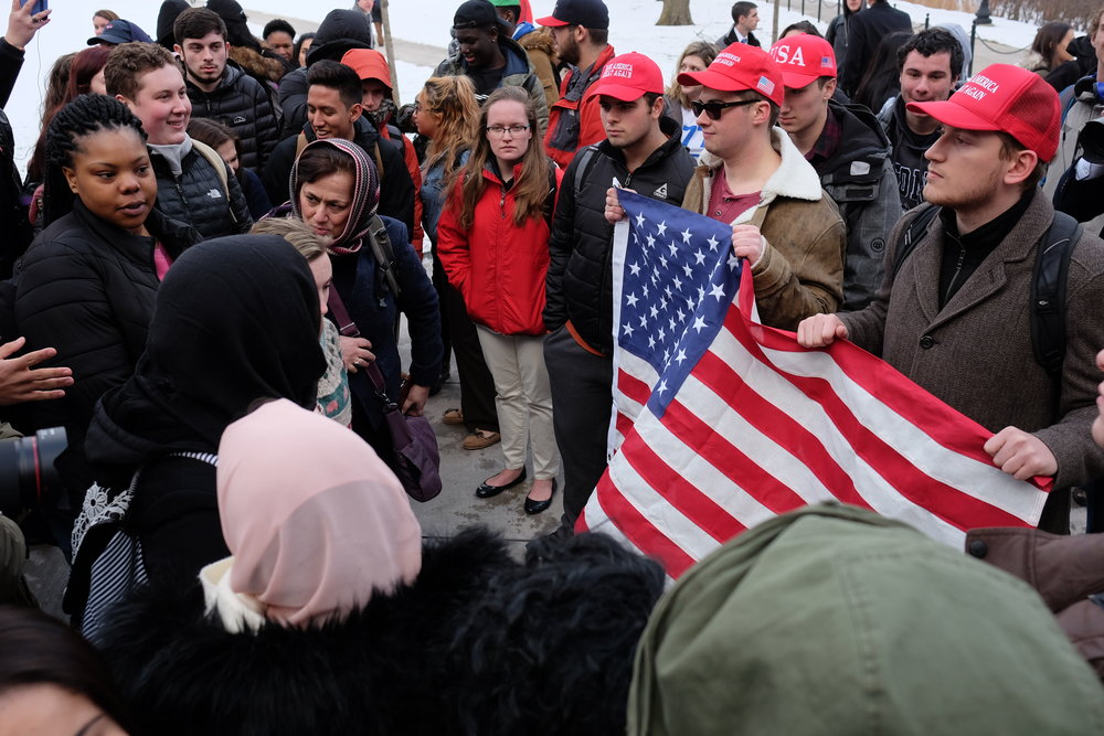 "Students and faculty gather to the steps of the Student Union to protest the recent Executive Order issued by President Donald Trump. Various speakers and activists pass the megaphone and speak out against the ""Muslim Ban"" issued last week. A small group of Republicans went to protest their side of the argument, holding an American flag. (Jon Sammis/The Daily Campus)"