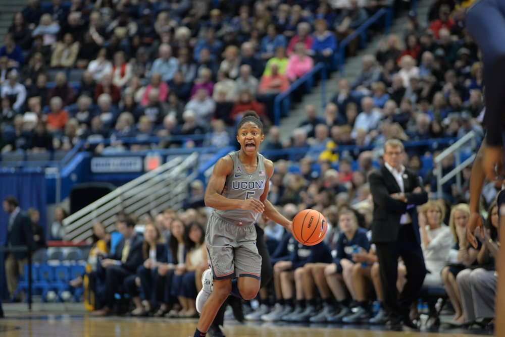Crystal Dangerfield runs the offense with Geno Auriemma looking on in the background. (Amar Batra/The Daily Campus)