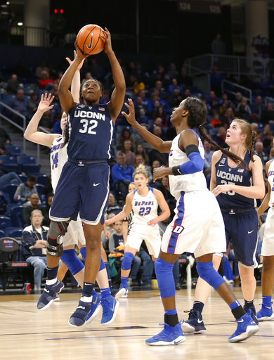 Connecticut forward Batouly Camara (32) shoots between DePaul's Rachel McLimore, left, and Chante Stonewall during the second half of an NCAA college basketball game Friday, Dec. 8, 2017, in Chicago. Connecticut won 103-69. (AP Photo/Charles Rex Arbogast)