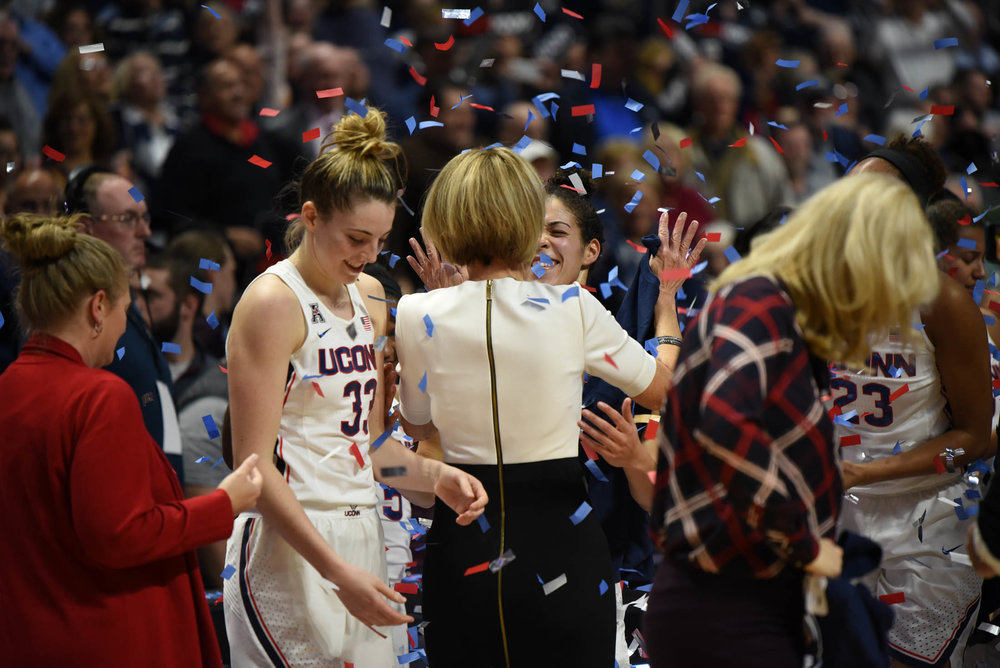 The Huskies celebrate after they defeat the Sooners making it Geno Auriemma And Chris Dailey's 1000th career win. (Charlotte Lao/The Daily Campus)