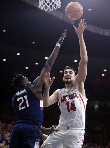 Arizona center Dusan Ristic (14) shoots over Connecticut forward Mamadou Diarra during the second half of an NCAA college basketball game Thursday, Dec. 21, 2017, in Tucson, Ariz. (AP Photo/Rick Scuteri)