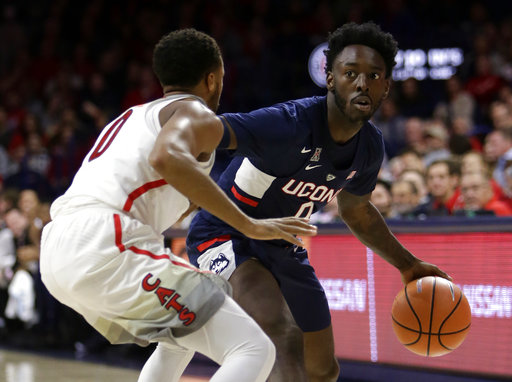 Connecticut guard Antwoine Anderson (0) drives on Arizona guard Parker Jackson-Cartwright during the first half of an NCAA college basketball game Thursday, Dec. 21, 2017, in Tucson, Ariz. (AP Photo/Rick Scuteri)
