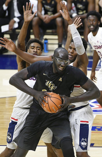Central Florida's Tacko Fall, center, is guarded by Connecticut's Isaiah Whaley, left, and Josh Carlton, right, during UConn's 62-53 win over UCF on Wednesday, Jan. 10, 2018 at Gampel Pavilion. (AP Photo/Jessica Hill)