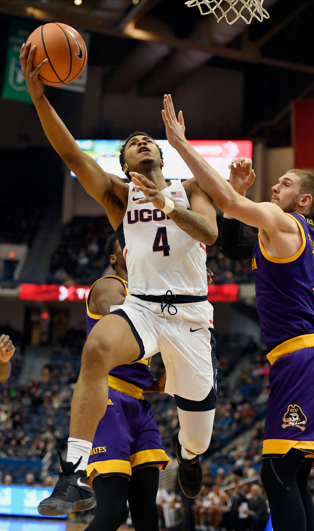 Connecticut's Jalen Adams, left, goes up for a basket as East Carolina's Dimitri Spasojevic, right, defends, during the first half of an NCAA college basketball game, Saturday, Jan. 6, 2018, in Hartford, Conn. (AP Photo/Jessica Hill)