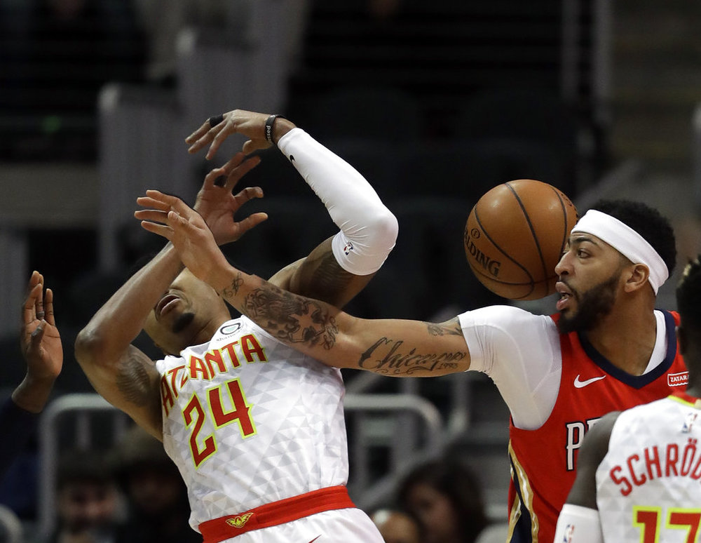 New Orleans Pelicans forward Anthony Davis (23) and Atlanta Hawks guard Kent Bazemore (24) battle for the ball during the first half of an NBA basketball game Wednesday, Jan. 17, 2018, in Atlanta. (AP Photo/John Bazemore)