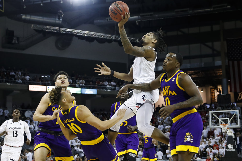 Cincinnati's Jacob Evans, center, shoots over ECU's Aaron Jackson (10) in the first half of an NCAA college basketball game, Saturday, Jan. 20, 2018, in Highland Heights, Ky. (AP Photo/John Minchillo)