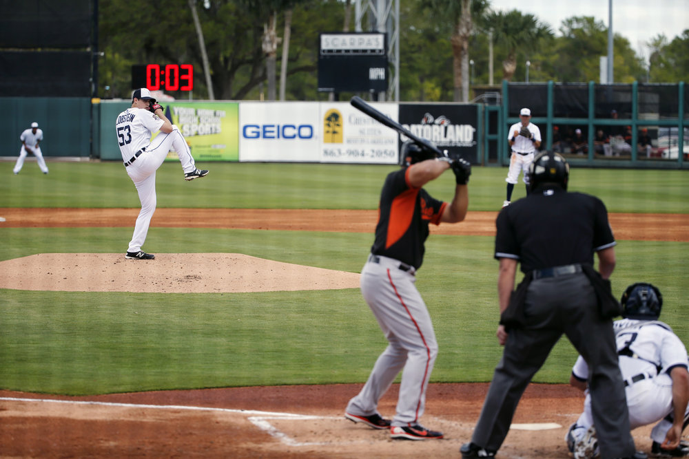 In this March 3, 2015, file photo, Detroit Tigers pitcher Kyle Lobstein, left, delivers his first pitch of the second inning to Baltimore Orioles' Matt Tulasosopo as the clock, background, counts down during a spring training exhibition baseball game in Lakeland, Fla. Major League Baseball has proposed the use of 20-second pitch clocks and limits on mound visits, a move that dares management to unilaterally impose the changes designed to speed pace of games. (AP Photo/Gene J. Puskar, File)