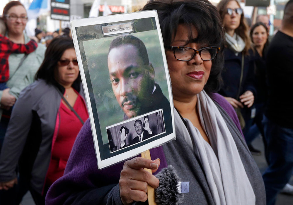 Val Scott holds up a photo of Martin Luther King Jr. during a march to mark the birthday of the slain civil rights leader in San Francisco, Monday, Jan. 15, 2018. (AP Photo/Jeff Chiu)