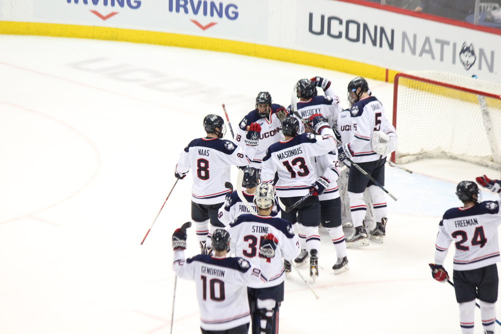 The Men's Hockey team celebrates their 3-2 win over UNH on Saturday at the XL Center (Ryan Murace/The Daily Campus).