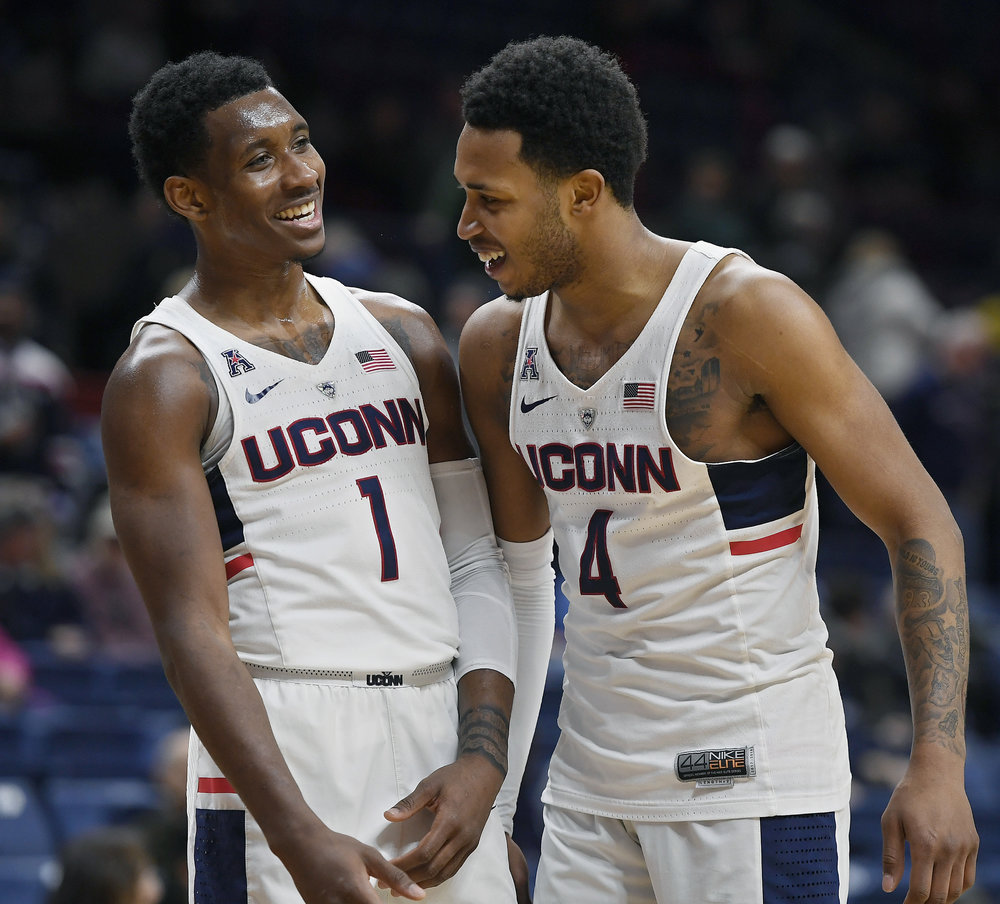 Connecticut's Christian Vital, left, and Jalen Adams, right, smile during final seconds of an NCAA college basketball game against SMU, Thursday, Jan. 25, 2018, in Storrs, Conn. (AP Photo/Jessica Hill)