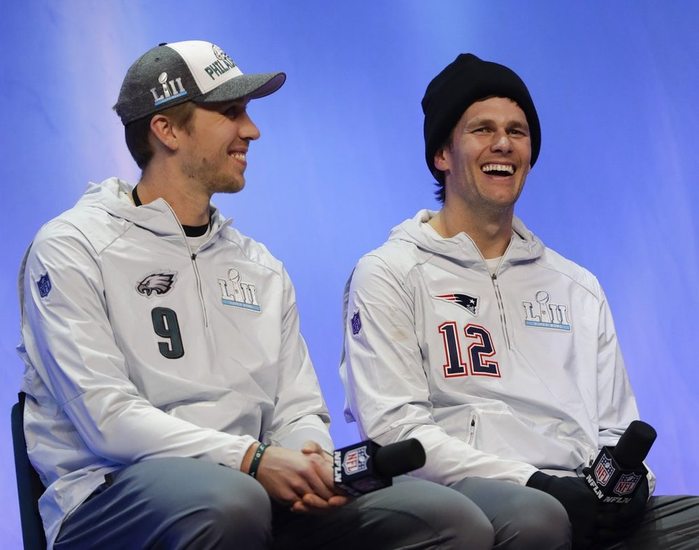 Philadelphia Eagles' Nick Foles and New England Patriots' Tom Brady answer questions during NFL football Super Bowl 52 Opening Night Monday, Jan. 29, 2018, at the Xcel Center in St. Paul, Minn. (AP Photo/Eric Gay)